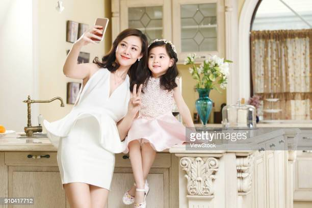 The fashionable mother and daughter in dress are taking pictures