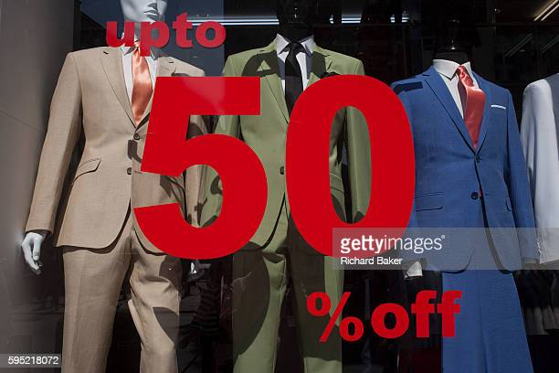 The fashionable styles of menswear suits worn by shop mannequins and discounted by 50% in the window of an Oxford Street window on 24th August 2016...