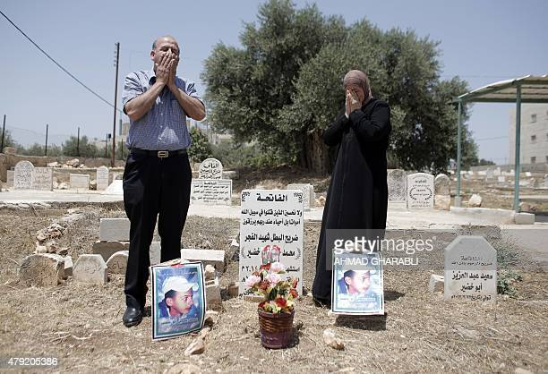 The father and mother of Palestinian teenager Mohammed Abu Khdeir pray at his grave as they mark one year anniversary since his killing by Israelis...