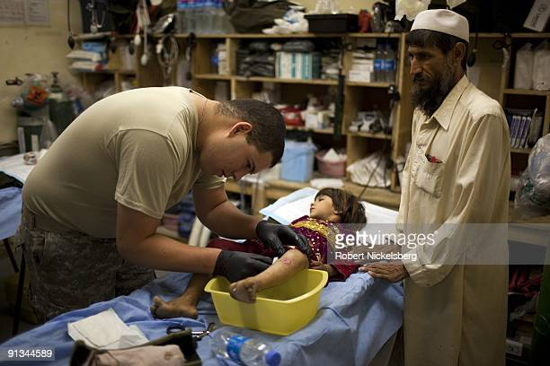 The father of a 4year girl Talwaza stands over as a US Army medic cleans a recent bullet wound at a clinic on Forward Operating Base Blessing in...
