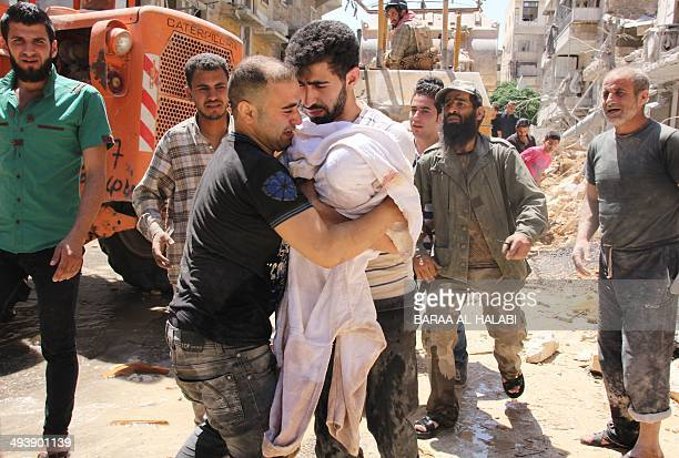 The father of a threemonth old girl whose body was pulled out of the rubble weeps as he approaches the rescuer to carry her following a barrel bomb...