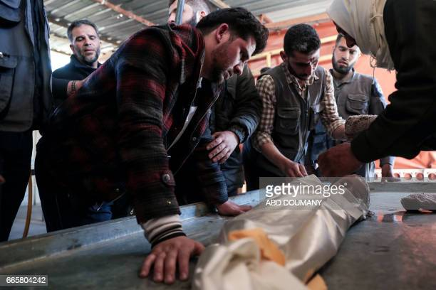 The father of oneyearold infant Amira grieves over her body as it lies in a makeshift morgue after she died in a reported air strike on the rebelheld...