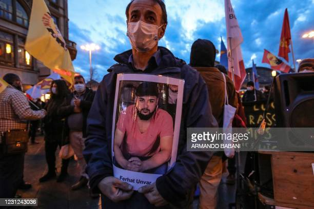 The father of victim Ferhat Unvar holds a portrait of his son as he takes part in a rally to commemorate the victims of the 2020 Hanau shooting in...