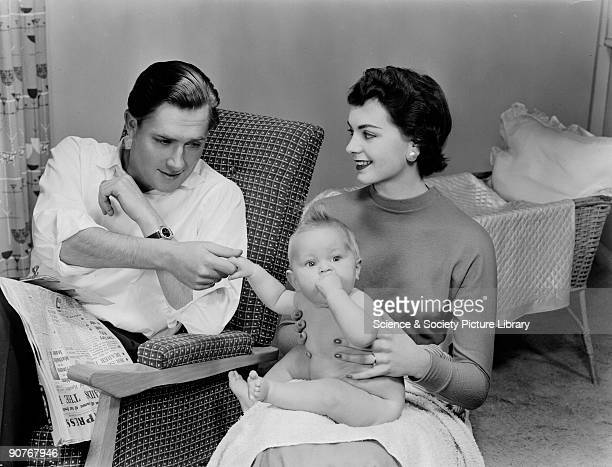 The father reaches gingerly over to touch the naked baby bathing and changing nappies clearly the preserve of the mother Photographic Advertising...
