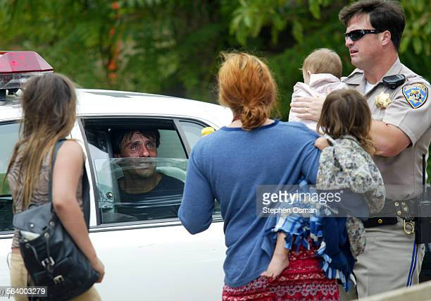 The father who was arrested after the pursuit talks with his family from the backseat of a LAPD patrol car CHP officer John Valenti holds the infant...