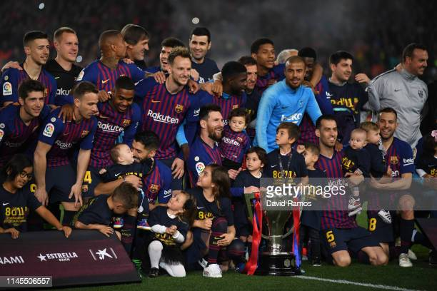 The FC Barcelona players pose with the La Liga trophy following their victory in the La Liga match between FC Barcelona and Levante UD at Camp Nou on...