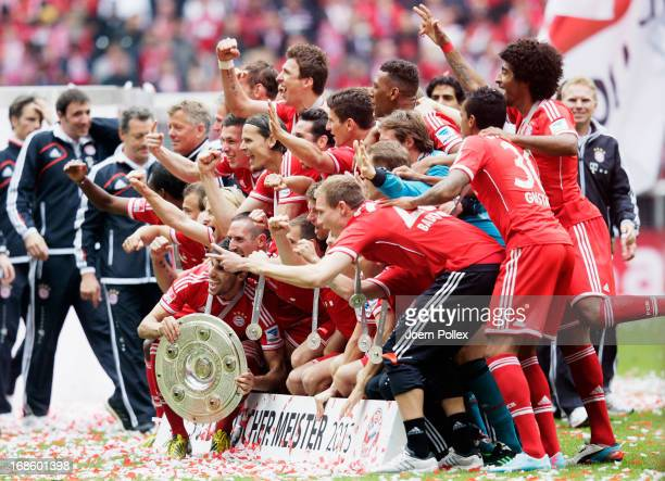 The FC Bayern Muenchen players celebrate with the Bundesliga trophy following their match against Augsburg at the Allianz Arena on May 11 2013 in...