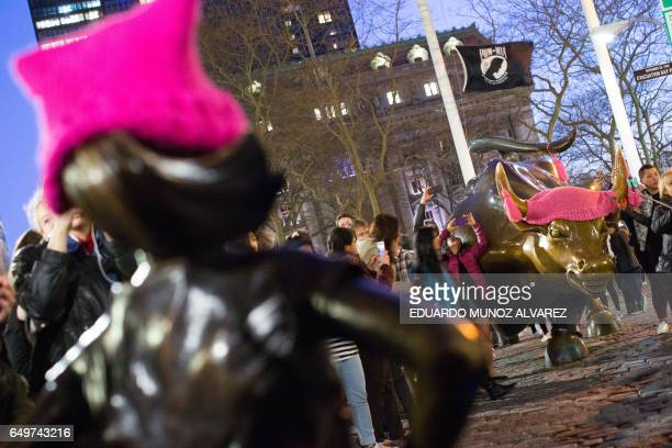 'The Fearless Girl' statue is seen facing the iconic Wall Street charging bull statue as part of a campaign to push companies to add women on their...