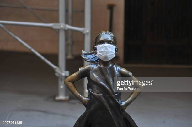 The 'Fearless Girl' statue stands across from the New York Stock Exchange wearing a coronavirus mask