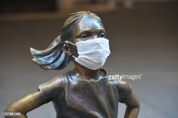 The 'Fearless Girl' statue stands across from the New York Stock Exchange wearing a coronavirus mask.