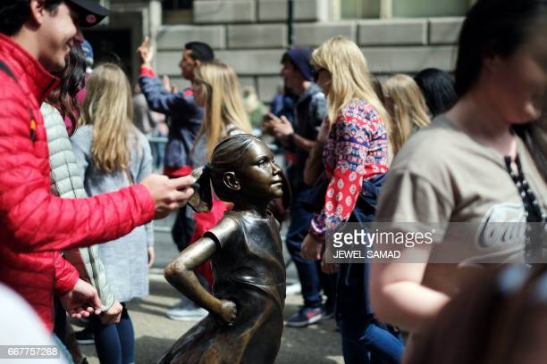 The 'Fearless Girl' statue stands facing the 'Charging Bull' as people walk past in New York on April 12 2017 A battle is heating up between two...