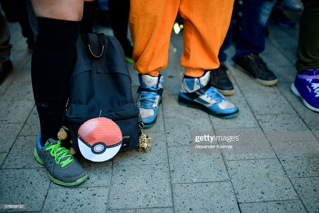 The feet and bags of young players are seen standing in the city centre of Hanover while holding their smartphones and playing 'Pokemon Go' on July 15, 2016 in Hanover, Germany. 1.200 players have participated in the night walk through the city centre until midnight. 'Pokemon Go' is a mobile game for smartphones, it uses advanced reality and geo-data to integrate the player in his search for new monsters or opponents within his location. The player now has to walk through the city, instead of spending time in front of a computer.