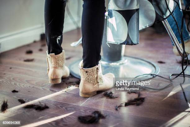 The feet of a hairdresser wearing pretty boots and hair cut on the floor in a hairdressing salon