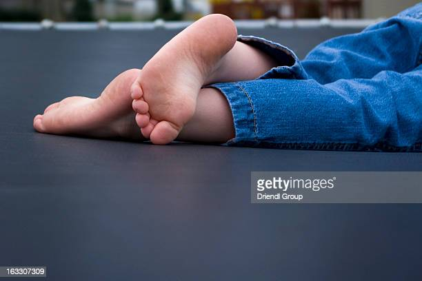 The feet of a little girl laying on a trampoline
