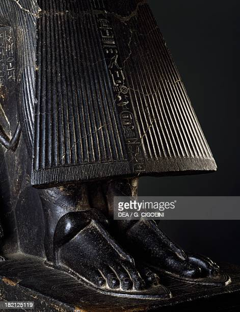 The feet of a pharaoh wearing woven palm leaf sandals crushing nine arches engraved in the base symbolising the enemies of Egypt detail of the group...