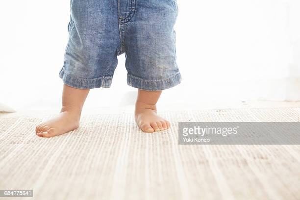 The feet of a standing baby.