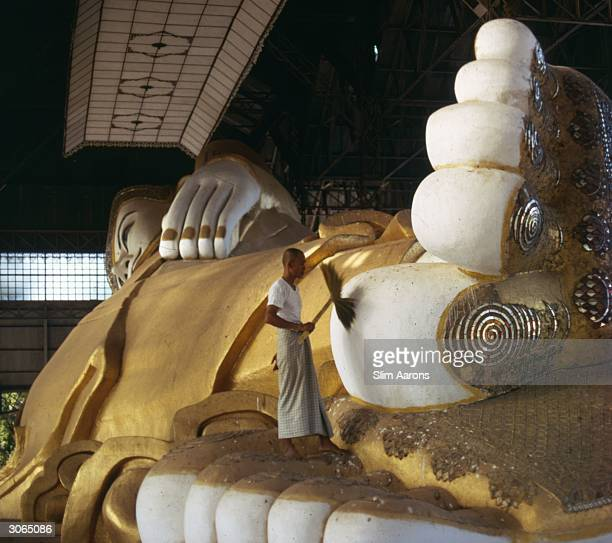 The feet of the reclining Buddha in Rangoon Burma being given a dust