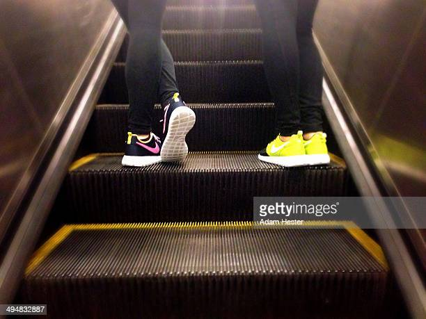 The feet of two women wearing Nike running shoes while riding on a escalator