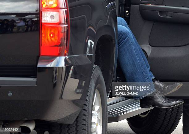 The feet of US Republican presidential candidate Mitt Romney are seen coming out of his car as he arrives to board his campaign plane at Tampa...