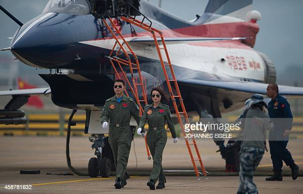 The female and a male pilot of a J10 fighter jet of the Bayi Aerobatic Team of PLA's Air Force walk after a flight at the Airshow China 2014 in...