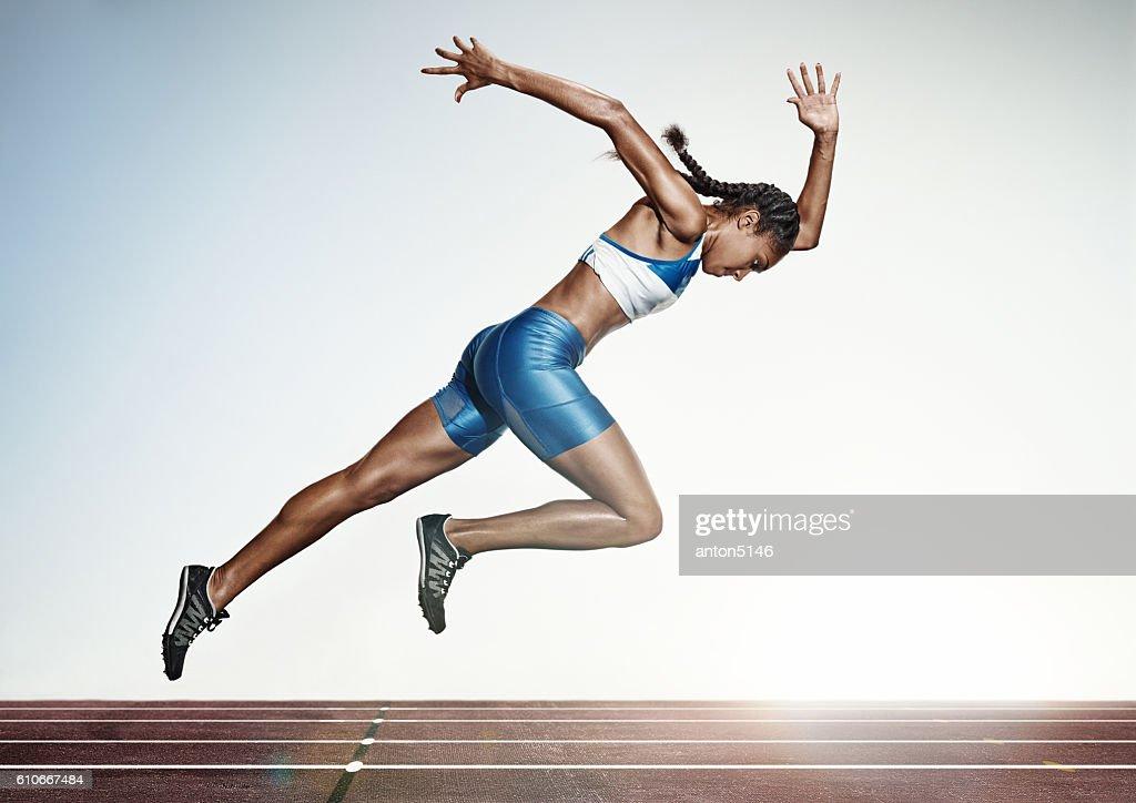 The female athlete running on runing track : Stock Photo