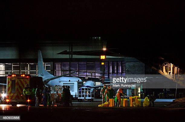 The female healthcare worker who returned from Sierra Leone to Glasgow is taken from an ambulance and loaded onto an aircraft at Glasgow...