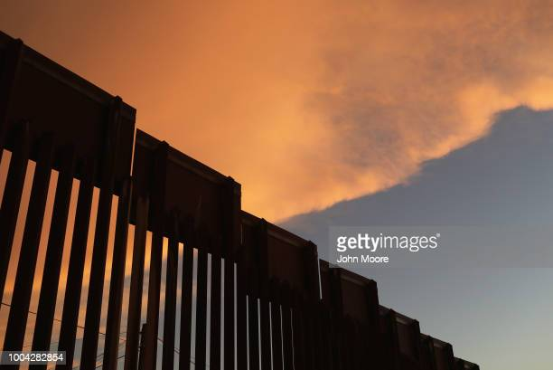 S Border Patrol agent watches over the USMexico border at dusk on July 22 2018 in Nogales Arizona President Trump has proposed replacing the fence...