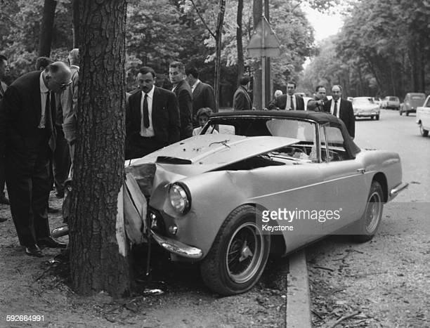 The Ferrari 250 GT car of diplomat and racing driver Porfirio Rubirosa crashed in to a chestnut tree being viewed by a group of men in suits after...