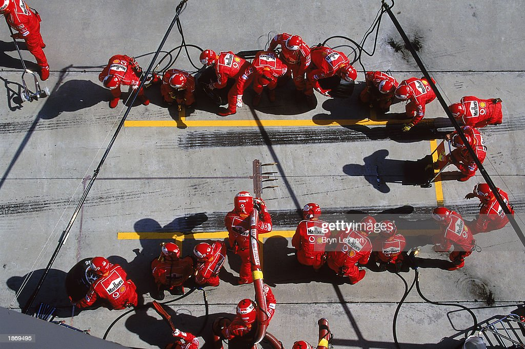 The Ferrari crew await a pit stop during the Formula One Malaysian Grand Prix held on March 23, 2003 at the Sepang International Circuit in Kuala Lumpur, Malaysia.