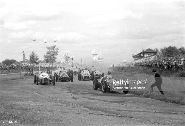 The Ferrari of Dorino Serafini leads the pack shortly after the start of the German Grand Prix at the Nurburgring, 20th August 1950. Right behind him...