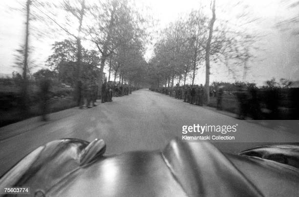 The Ferrari of Peter Collins and photographer Louis Klemantaski roars past the crowds and into the dawn during the Mille Miglia May 1957 The crowds...