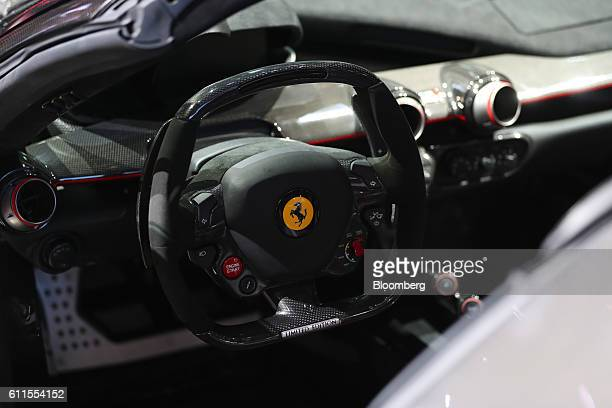 The Ferrari prancing horse logo sits on the steering wheel inside the LaFerrari Aperta automobile, produced by Ferrari NV, during the second press...