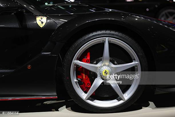 The Ferrari prancing horse logo sits on the wheel hub of the LaFerrari Aperta automobile, produced by Ferrari NV, during the second press day of the...