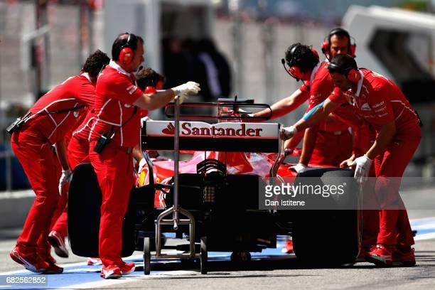 The Ferrari team push Sebastian Vettel of Germany driving the Scuderia Ferrari SF70H in the Pitlane during final practice for the Spanish Formula One...