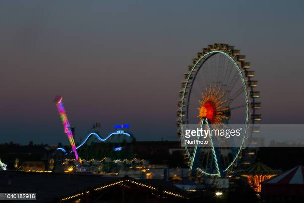 The ferris wheel and the roller coaster seen in a long time exposure and zoom burst effect on Day 4 of the Oktoberfest The Oktoberfest or Wiesn in...
