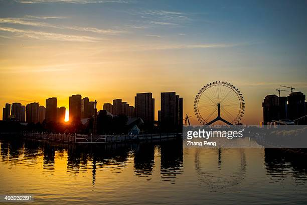 The ferris wheel called the Tianjin Eye is reflected on the Haihe river at sunset With its fast economic development Tianjin will surpass Hong Kong...