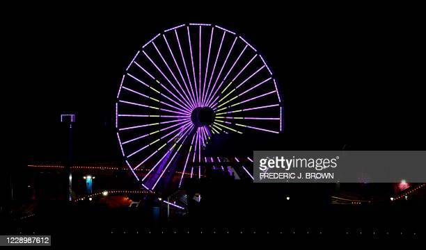 """The Ferris wheel on the Santa Monica Pier in Santa Monica, California is lit in purple and gold with the letters """"LA"""" on October 9, 2020 for Game 5..."""