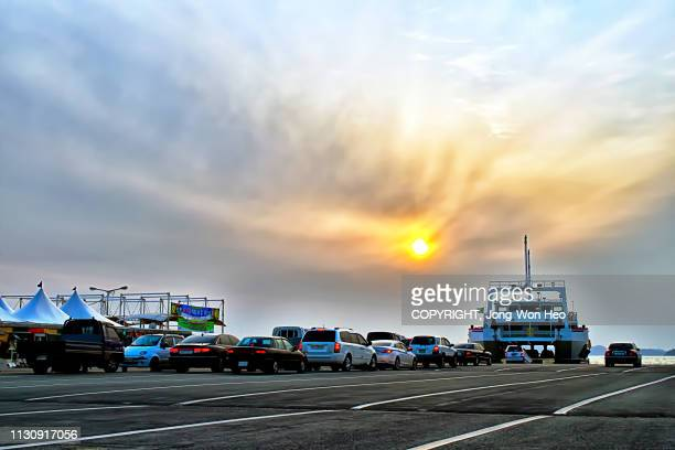 the ferry boarding vehicles before departure in the sunset - ferry stock pictures, royalty-free photos & images