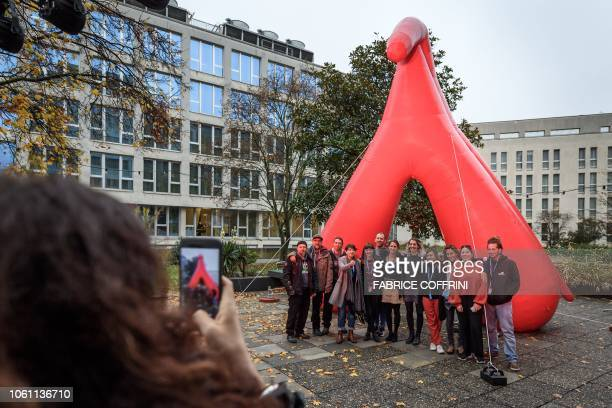 The festival staff of Les Creatives poses in front of a 7 meter high inflated sculpture in the shape of a clitoris at the entrance of the...