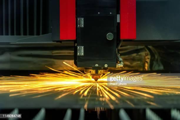 the fiber laser cutting machine cutting the sheet metal plate with the sparking light. hi-technology manufacturing concept. - lisa sparks - fotografias e filmes do acervo