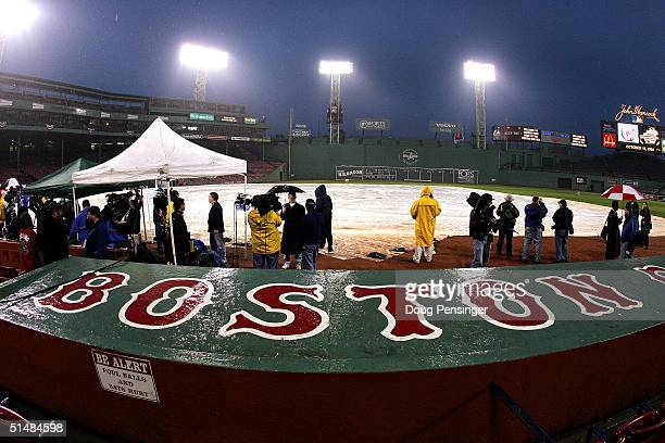 The field of play is covered as rain falls before the New York Yankees take on the Boston Red Sox in game three of the American League Championship...