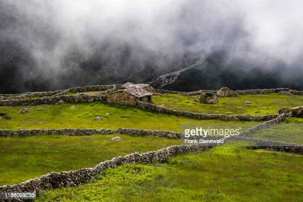 The fields of the small village are surrounded by stone walls mountainous landscape covered in monsoon clouds in the distance