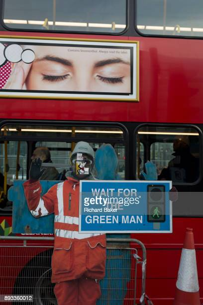 The figure of a construction worker warning pedestrians to cross sensibly and a passing bus on 12th December 2017 in London England