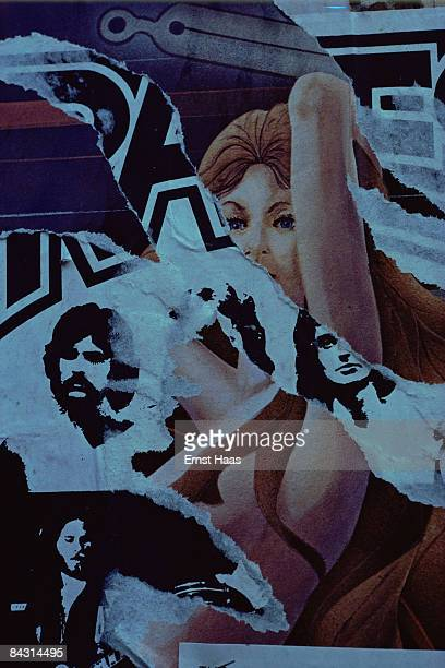 The figure of a woman and three male faces among the patterns formed by layers of torn posters, USA, circa 1970.