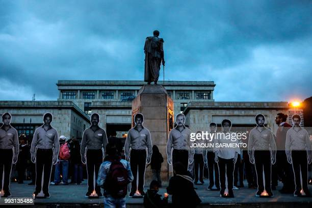 The figures of murdered activists are placed next to candles during a protest aat the Bolivar square in Bogota on July 6 2018 The UN urged the...