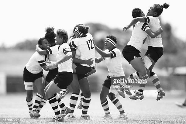 The Fiji girls rugby sevens team celebrate after defeating the Cook Islands in the girls rugby sevens bronze medal match at the Apia Park Sports...