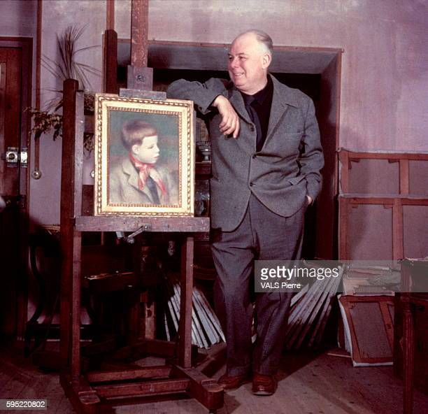 the film director Jean Renoir poses near his portrait painted by his father Auguste Renoir at the art gallery DurandRuel in Paris on 1958