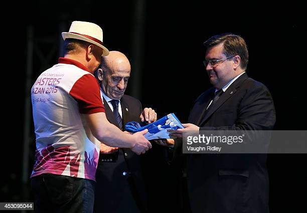 The FINA Flag is presented by FINA President Dr Julio C Maglione and Montreal Mayor Denis Coderre to a member of the Kazan 2015 Organizing Committee...