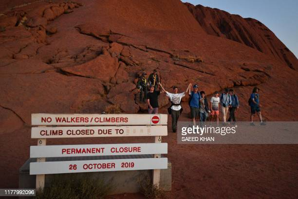 The final batch of tourists to climb Uluru, also known as Ayers Rock, return at day's end marking the start of a permanent ban on climbing the...