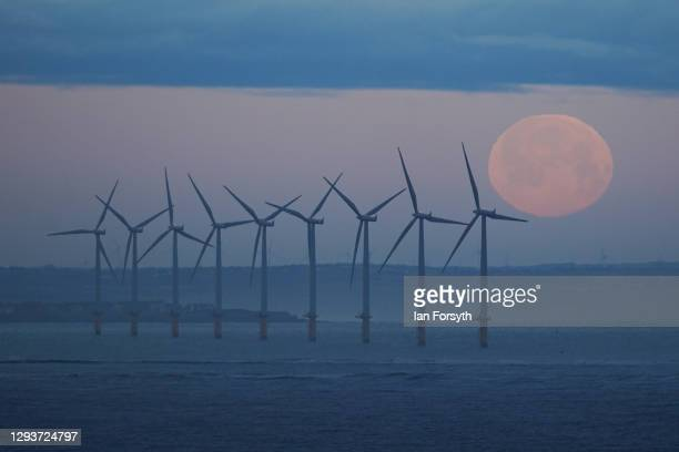 The final full moon of 2020 known as the Cold moon begins to set behind the offshore wind farm at Redcar on December 30, 2020 in Saltburn By The Sea,...